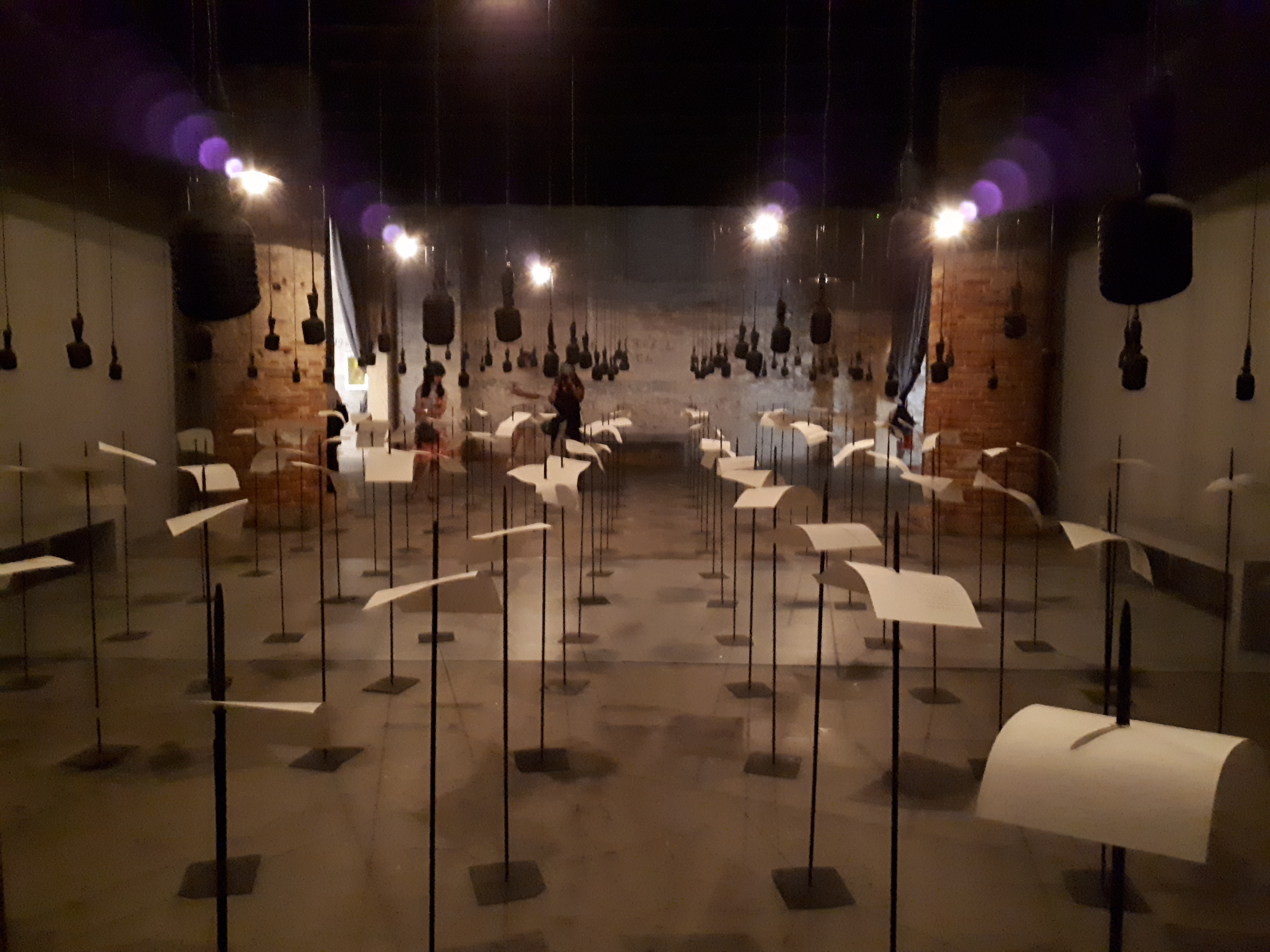 shilpa-gupta-for-in-your-tongue-i-cannot-fit-sound-installation-with-100-speakers-microphones-printed-text-and-metal-stands-2017-18