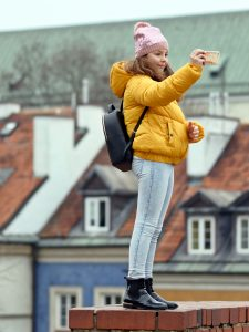 woman-in-yellow-puffer-jacket-and-blue-jeans-holding-3280807