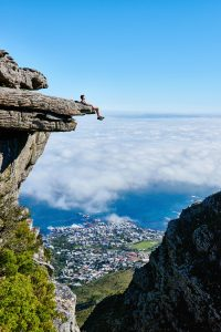 person-sitting-on-mountain-cliff-1659438
