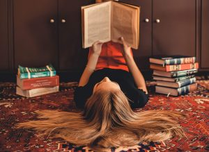 woman-lying-on-area-rug-reading-books-2899918