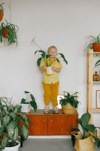 boy-in-yellow-jacket-and-pants-standing-beside-green-plants-3771666