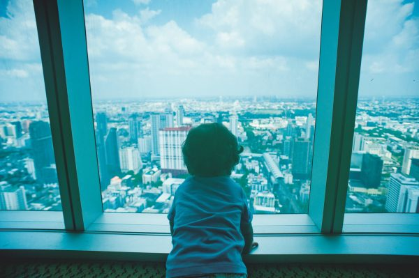 toddler-looking-through-clear-glass-window-1031795