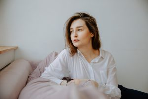 woman-in-white-dress-shirt-sitting-on-couch-3958877