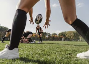 back-view-women-hands-trying-to-catch-a-rugby-ball