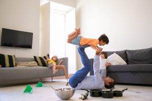 Caucasian dad holding son on legs and lying on carpet. Happy cute boy flying in living room with help of father. Cute kids playing together near bowl and pans. Childhood and weekend concept