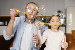 front-view-of-father-and-daughter-playing-with-soap-bubbles