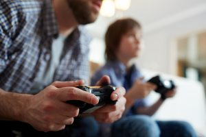 Young man with joystick playing video game on background of his son