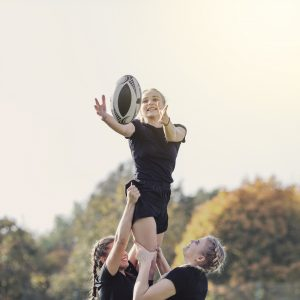 girl-catching-a-ball-helped-by-her-team-mates