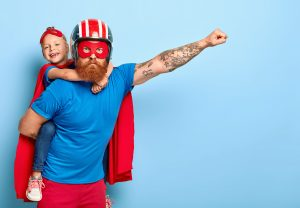 Powerful dad gives piggy back to child, demonstrates courage, makes flying gesture, wears helmet, red mask, cape, have fun together, stand against blue wall with empty space, brave help someone else