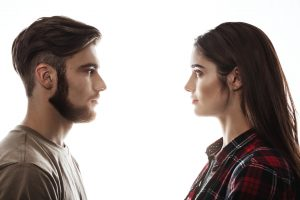Side view. Closep portrait of man and woman facing each other with eyes open.