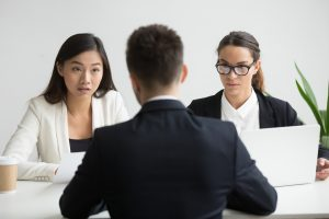 Serious unconvinced diverse hr managers interviewing male job applicant, doubtful strict female recruiters looking uncertain distrustful rejecting vacancy candidate, bad first impression concept