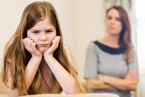 Daughter sitting upset with her mother in living room