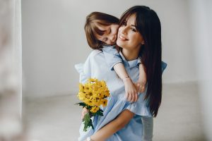 Child give mother flowers. Family at home. Mothers day