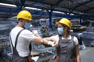 People working at factory touching with elbows and greeting due to corona virus and infection.