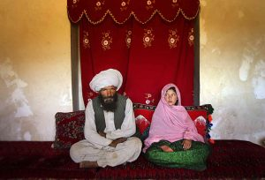 Faiz, 40, and Ghulam, 11, sit in her home prior to their wedding in rural Afghanistan. Ghulam said she is sad to be getting engaged as she wanted to be a teacher. Before she was made to drop out of school her favorite class was Dari, the local language. Married girls are seldom found in school, limiting their economic and social opportunities.