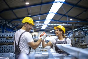 Factory workers handshaking each other at production line.