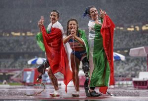 epa09447202 A handout photo made available by OIS/IOC shows winner Ambra Sabatini of Italy celebrating with runner up Martina Caironi of Italy and third place Monica Graziana Contrafatto of Italy at the finish of the Athletics Women's 100m - T63 Final in the Olympic Stadium at the Tokyo 2020 Paralympic Games, Tokyo, Japan, Saturday 04 September 2021.  EPA/Thomas Lovelock for OIS HANDOUT   EDITORIAL USE ONLY/NO SALES