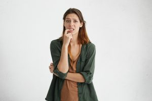 Horizontal portrait of confused woman with warm dark eyes, dark dyed straight hair and long face holding her finger on teeth having difficult choice frowning her eyebrows not knowing what to choose
